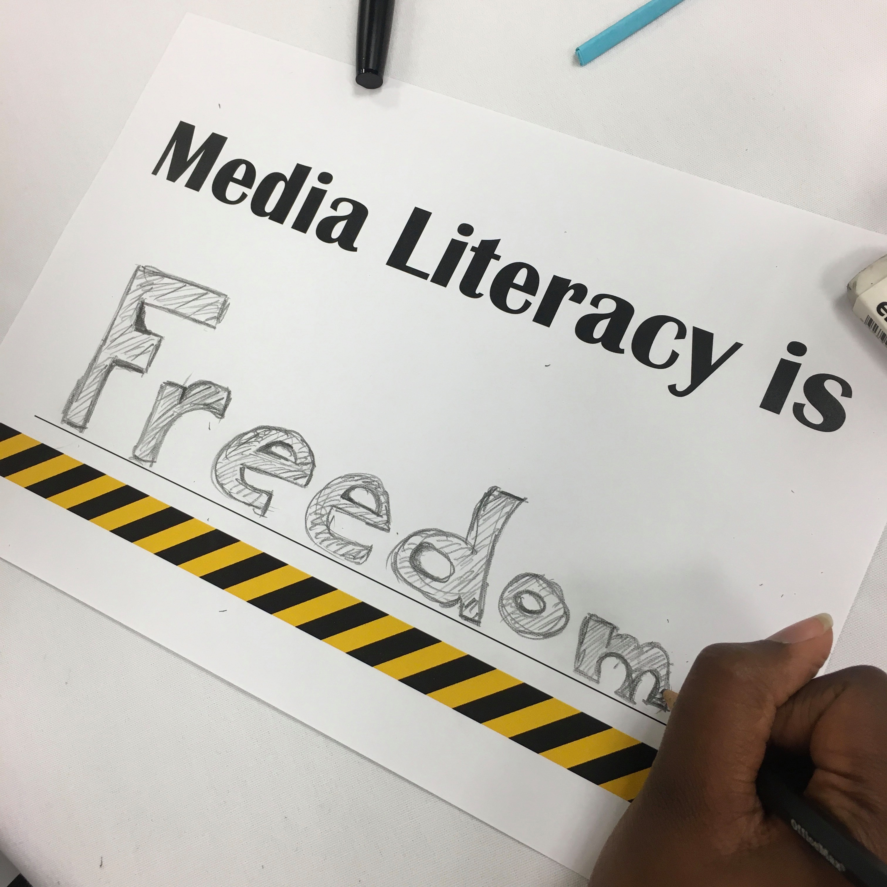 The blank space on a worksheet reading 'Media Literacy is….' has been filled out with the word 'Freedom' in strong, bold lettering. A hand holding a pencil is shown in the lower right corner putting the finishing touches on the word.