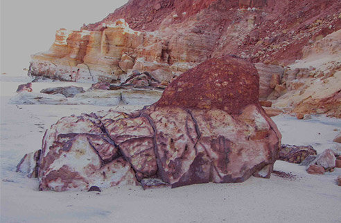 James Price Point speaks - (c) Deborah Wall, 2010. Red coloured rocks and cliffs in the sand.