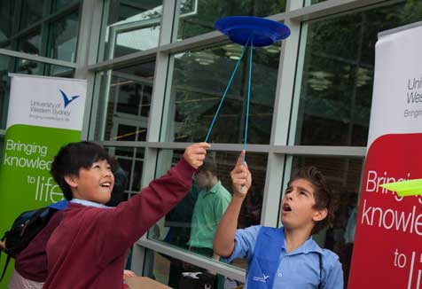 Students balance plates on a stick