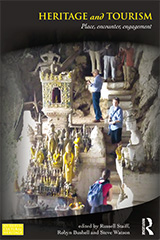 The cover of the book Heritage and Tourism which shows tourists at an Asian site where there are statues carved into the rock.