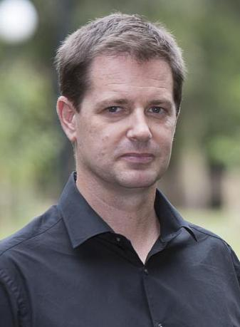 Should-up photo of Chris Gibson wearing a black collared shirt