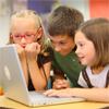 three school children having fun working on a computer