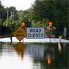 """A flooded road with the signs """"High Water"""" and """"Road Closed"""""""