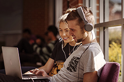 Two students looking at a computer screen with headphones