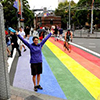 Thumbnail image of a woman standing on a rainbow coloured street crossing.