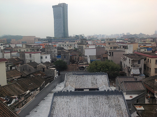 Looking out over rooftops in Zhongshan. Amongst the small dwellings stands one tall building.