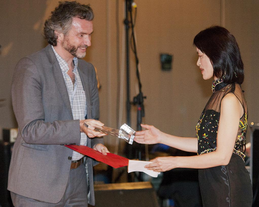 Adam presenting a glassed award to Xiaoying