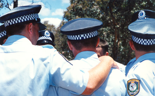Police officers console each other