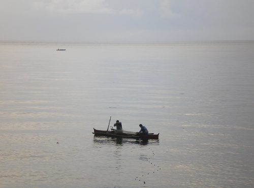Two men sit in a small boat in the water.