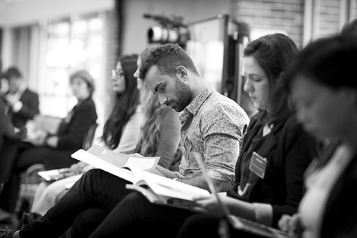 A black and white photo of the audience listening to the presentations with a focus on two people who are looking at their booklets.