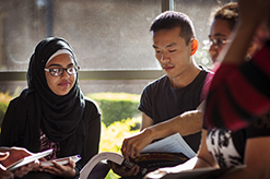 Students sitting and reading a text book