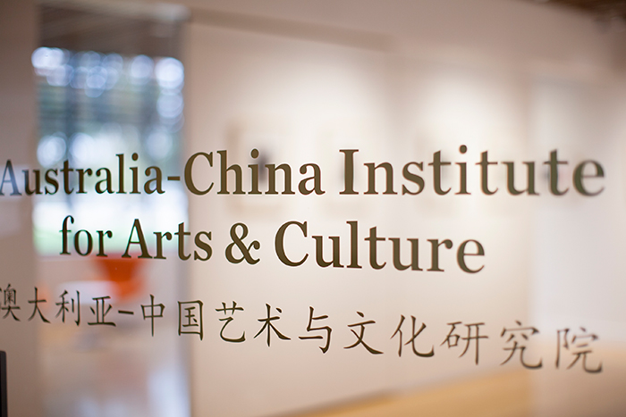 Closeup photo of glass door at entrance to Australia-China Institute for Arts and Culture with the Institute name written in English and Chinese on the glass.