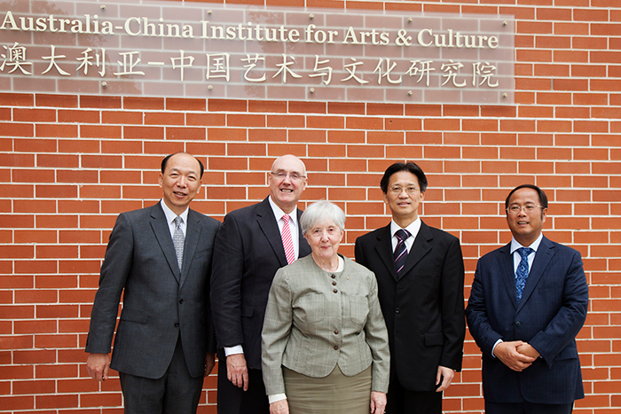 Barney Glover, Jocelyn Chey and three visitors stand in front of the Australia-China Institute for Arts and Culture sign and brick wall.