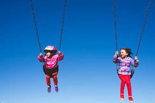 A photo of two children on swings against a blue sky.