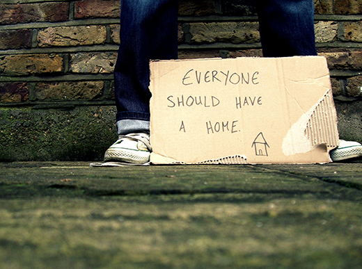 A photo of pair of legs standing against a brick wall. In front a piece of cardboard reads 'Everyone should have a home' with a drawing of a house.