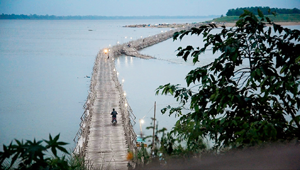 A motorcycle drives over the 1.5km bamboo bridge across the Mekong River.
