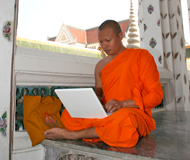 A Buddhist monk sitting down using a laptop.