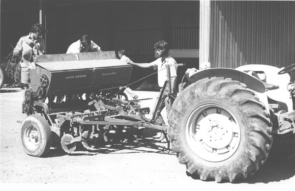 A tractor with students filling an attached John Deere Grassland (seed) Drill [Hawkesbury Agricultural College (HAC)]