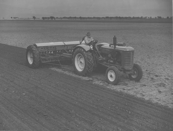 Ploughing a field with a tractor pulling farm machinery supplied by HV McKay Massey Harris Pty Ltd [Hawkesbury Agricultural College (HAC)]