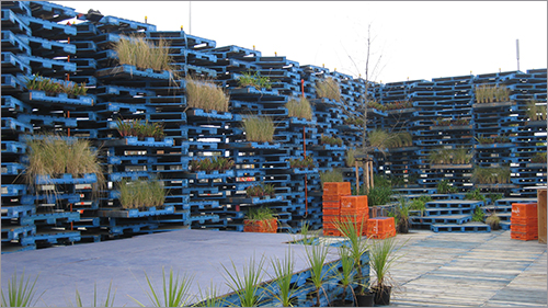 A pavilion made with blue wooden pallets. There are some plants in the pallets. Seating is in the form of orange plastic crates.