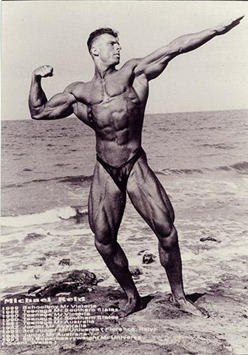 Staff Member - Michael Reid - Body building pose on a beach (P3642)