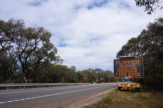 A sign on the side of a road reads 'Planned burns reduce fire risk'.