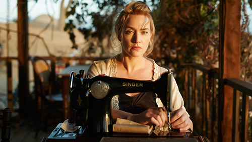 Scene from the movie The Dressmaker - Kate Winslet sits at a Singer sewing machine on a wooden veranda.