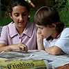 Two young children reading the newspaper