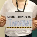 Hands hold a worksheet which has been completed to read 'Media Literacy is Important'.