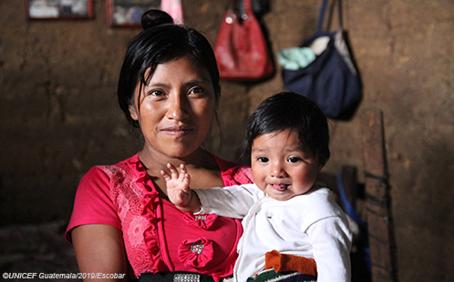 A mother, facing the camera, holds her baby. Photo ©UNICEF Guatemala/2019/Escobar.