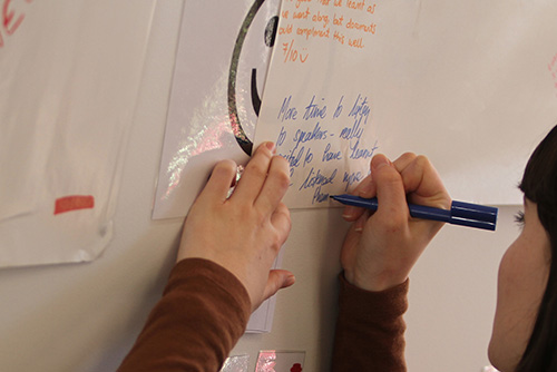 A girl writing on paper on a white board.