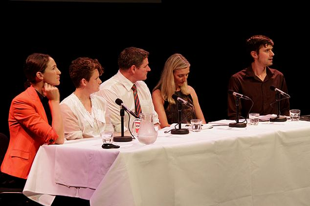 Keith sitting at a white table with four other panelists, three women and 1 man