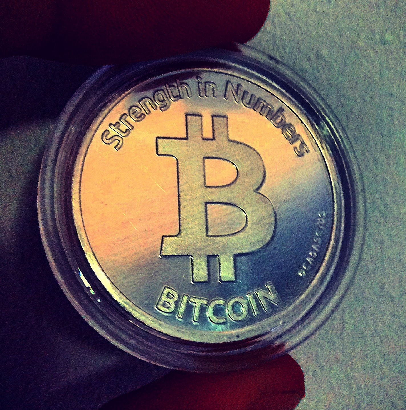 fingers holding a bitcoin