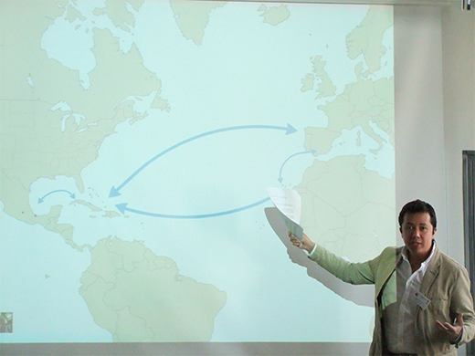 Alejandro Miranda Nieto giving a presentation - gesturing at a slide on a screen which shows a map of the world and arrows between Mexico, Europe, and across the North Atlantic Ocean.