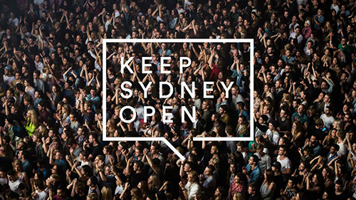 Photo looking down on a crowd at night with the Keep Sydney Open white logo over it (a rectangle with a small section of the bottom line open on an angle).