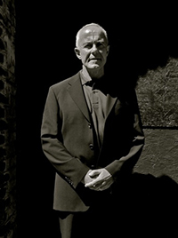Black and white photo of Professor Dick Hobbs wearing a suit standing against a brick and concrete wall.