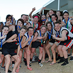 With medals around their necks, members of a women's AFL team smile for the camera, making 'Number 1' signs with their hands.