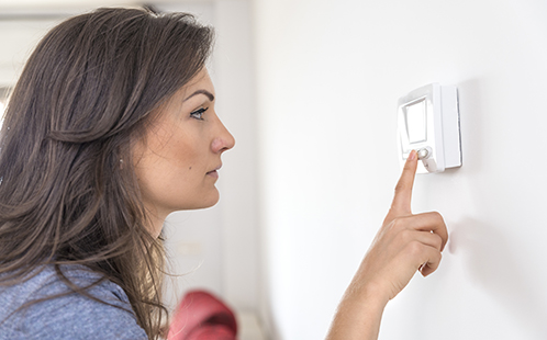 Woman adjusting air-conditioning inside the home