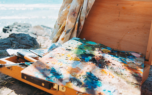 An abstract painting on canvas and a wooden box of art supplies sits on the rocks near the ocean.
