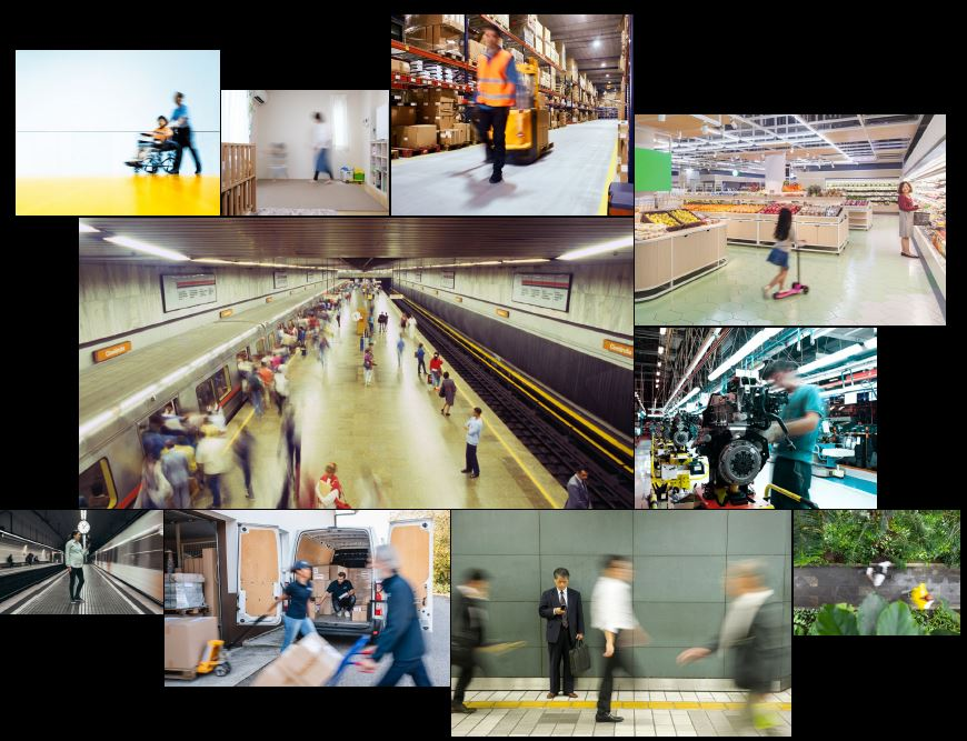 This image is an arrangement of ten smaller images in different sized boxes. Most of the people in the photos are blurred and indistinct, indicating movement. The smaller images are: a person in a wheelchair being pushed by another person; a person walking in a room that may be a child's nursery; a person and a machine in the aisle of a warehouse; a woman and a child on a scooter in the fruit and vegetable section of a supermarket; a person using a machine in a factory; a bird's eye view of two people passing each other on a garden path; men dressed in business attire walking past each other including one man who has stopped to look at the mobile phone in his hand; a delivery worker crouching in the back of a loaded van, while other delivery workers move trolleys loaded with boxes in front of the van's open doors; a woman standing on a platform as a train moves past; and two dozen or so commuters milling around on a different platform, some of whom are boarding a train while others wait for another train on the opposite platform.