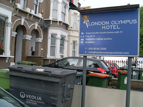 A sign outside a hotel reads 'London Olympus hotel'. There are overflowing rubbish bins on the street directly outside.