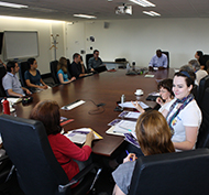 Handel Wright presents at the ICS Seminar Series. The photo shows attendees sitting around table.