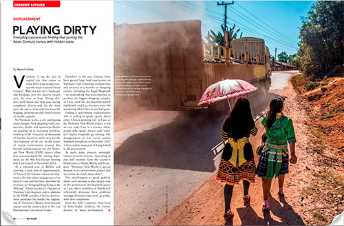 The first spread of Kearrin Sims' article in Globe magazine. Includes a photo of a Chinese construction truck driving through a small village in Laos.