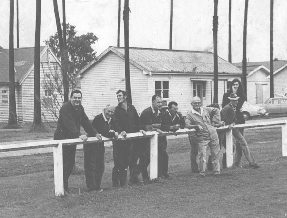 Staff members leaning on the fence near the oval [Hawkesbury Agricultural College (HAC)]