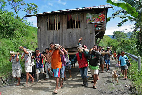 A group of men walk up a road towards the camera, carrying a wooden house on their shoulders.