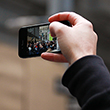 A thumbnail image of a hand holding a mobile phone in the air with a crown of people pictured on the screen.