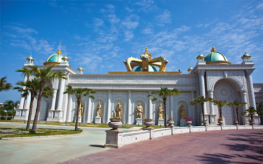Cream-coloured casino building with palm trees and gold and turquoise painted domes and crown on the roof and gold-coloured statues at the front.