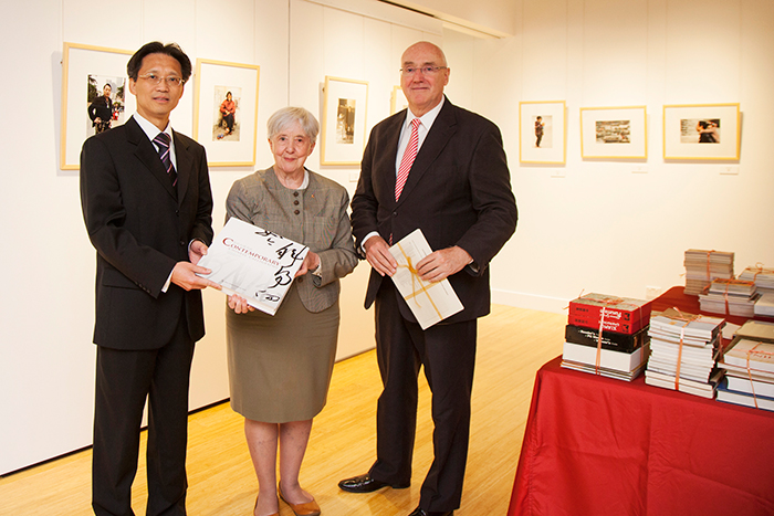 Barney Glover, Jocelyn Chey and visitor stand inside the Institute holding donated books. Books are sitting on a table beside them and artwork hangs on the walls.