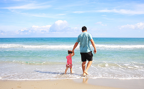 Dad and daughter walking on the beach