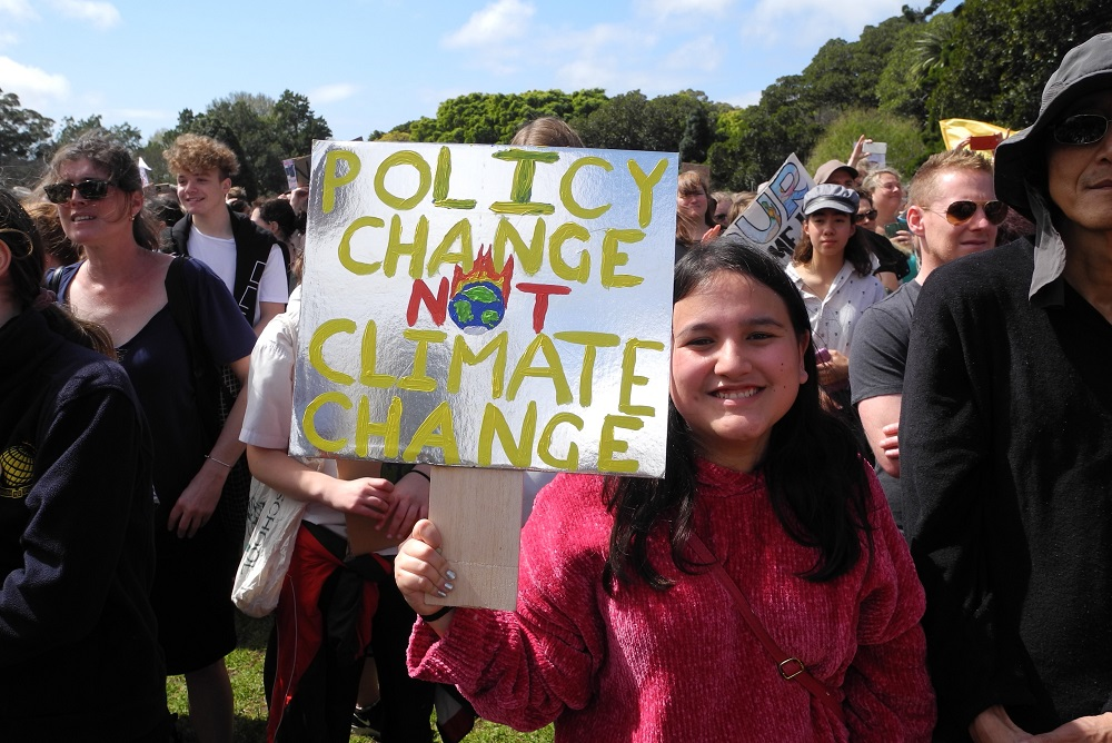 A young person in amongst a crowd holds a sign saying 'policy change not climate change'.